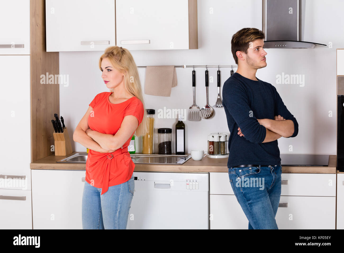 Sad Young Couple With Relationship Difficulties Talking About Infidelity And Divorce In Kitchen - Stock Image