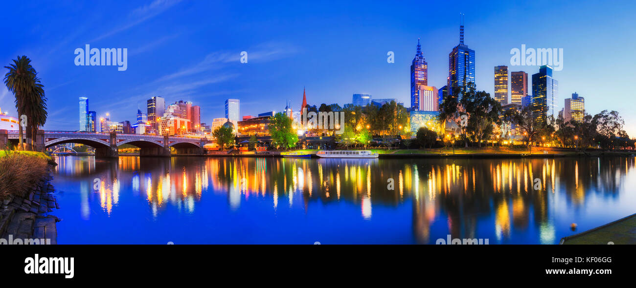 Blur colourful sunrise over Melbourne city CBD with bright downtown lights reflecting in still waters of Yarra and - Stock Image