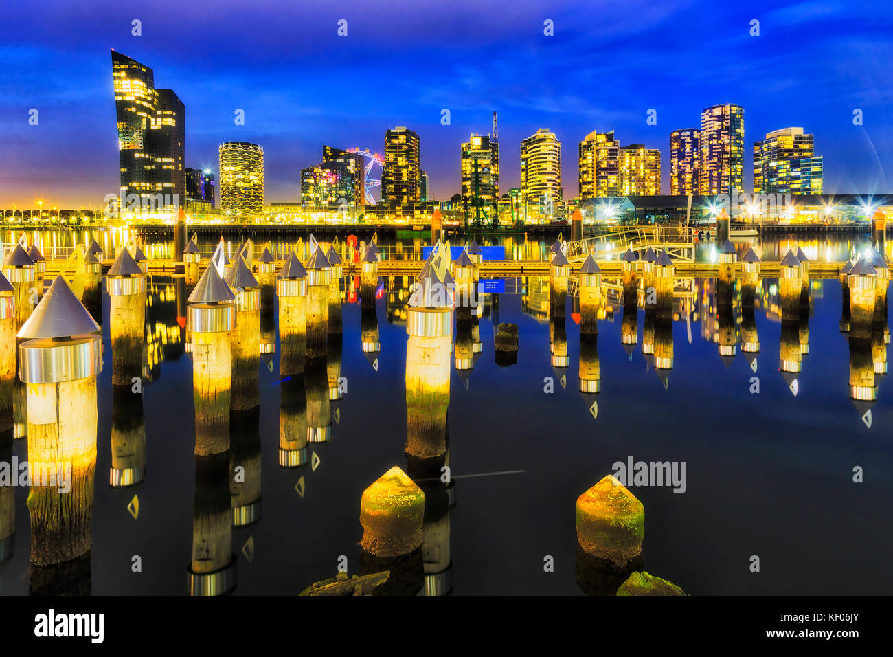 Matrix of timber jetty poles pinning out of still waters of Yarra river at Melbourne's docklands marina and - Stock Image