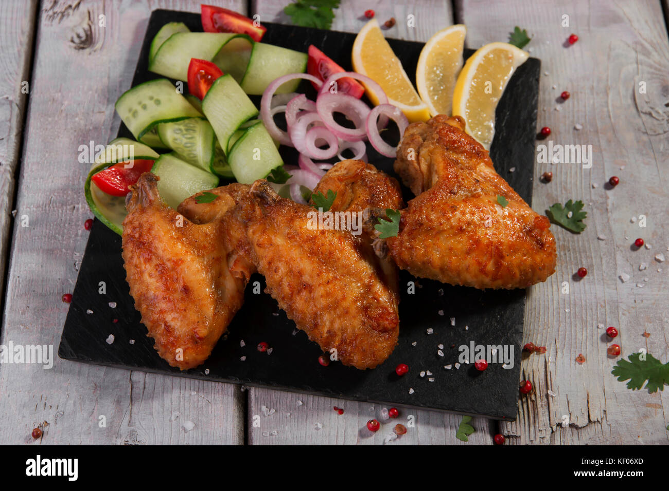 fried chicken wings with vegetables - Stock Image