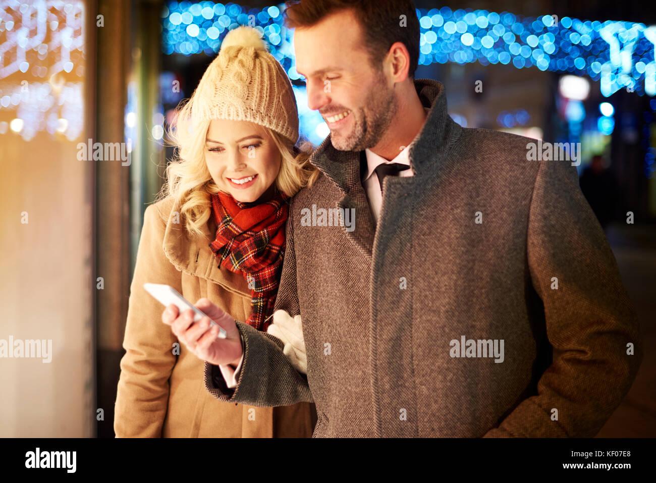 Waist up of couple using phone outdoors - Stock Image