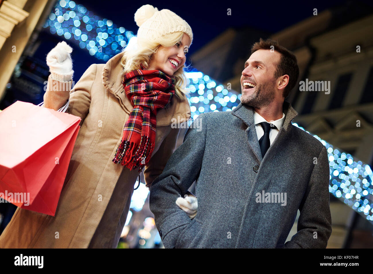 Photography of cheerful couple with shopping bags - Stock Image