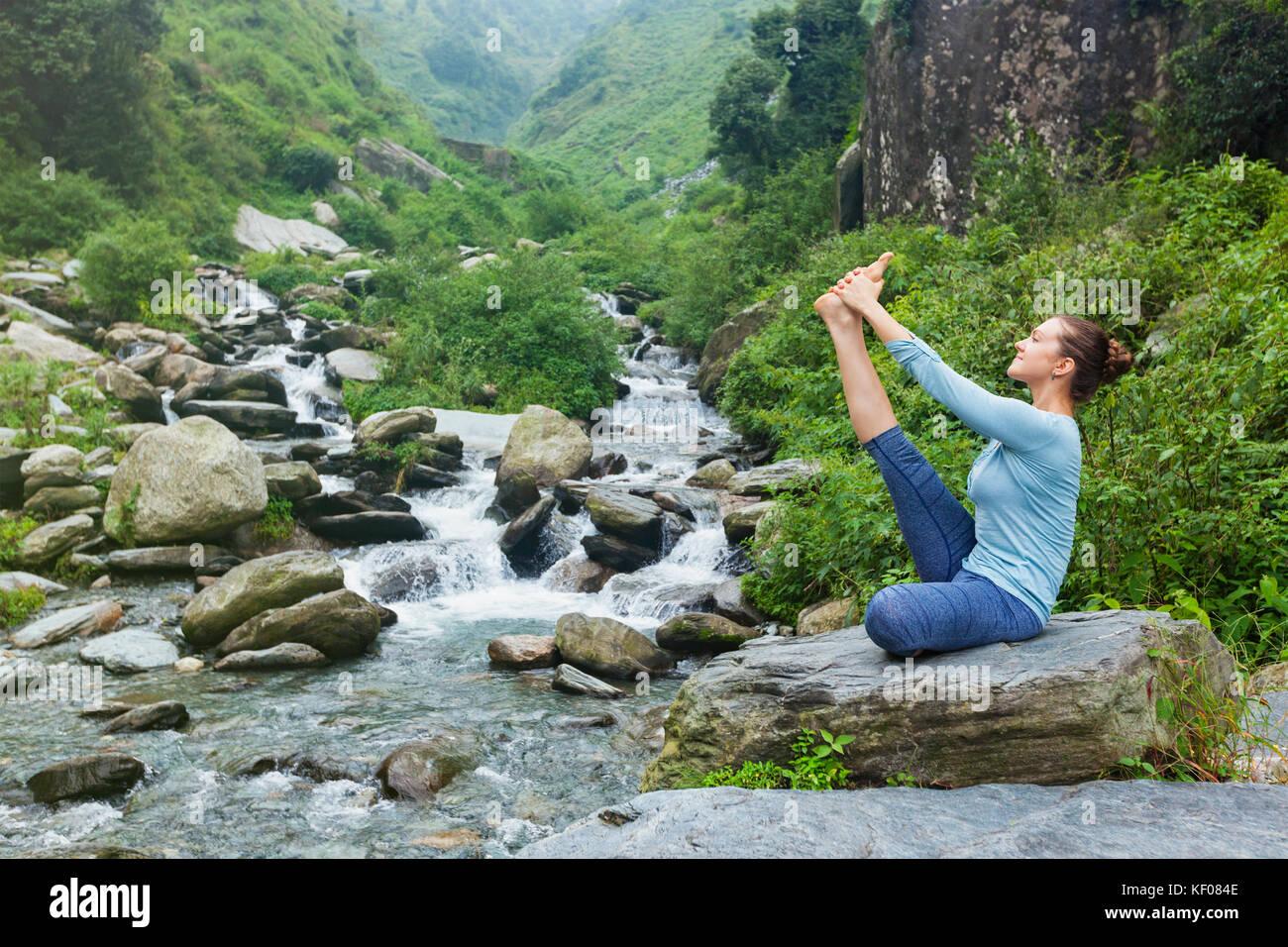 Woman doing Ashtanga Vinyasa Yoga asana outdoors - Stock Image