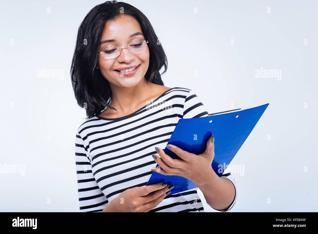 Upbeat woman studying documents in a blue sheet holder - Stock Image