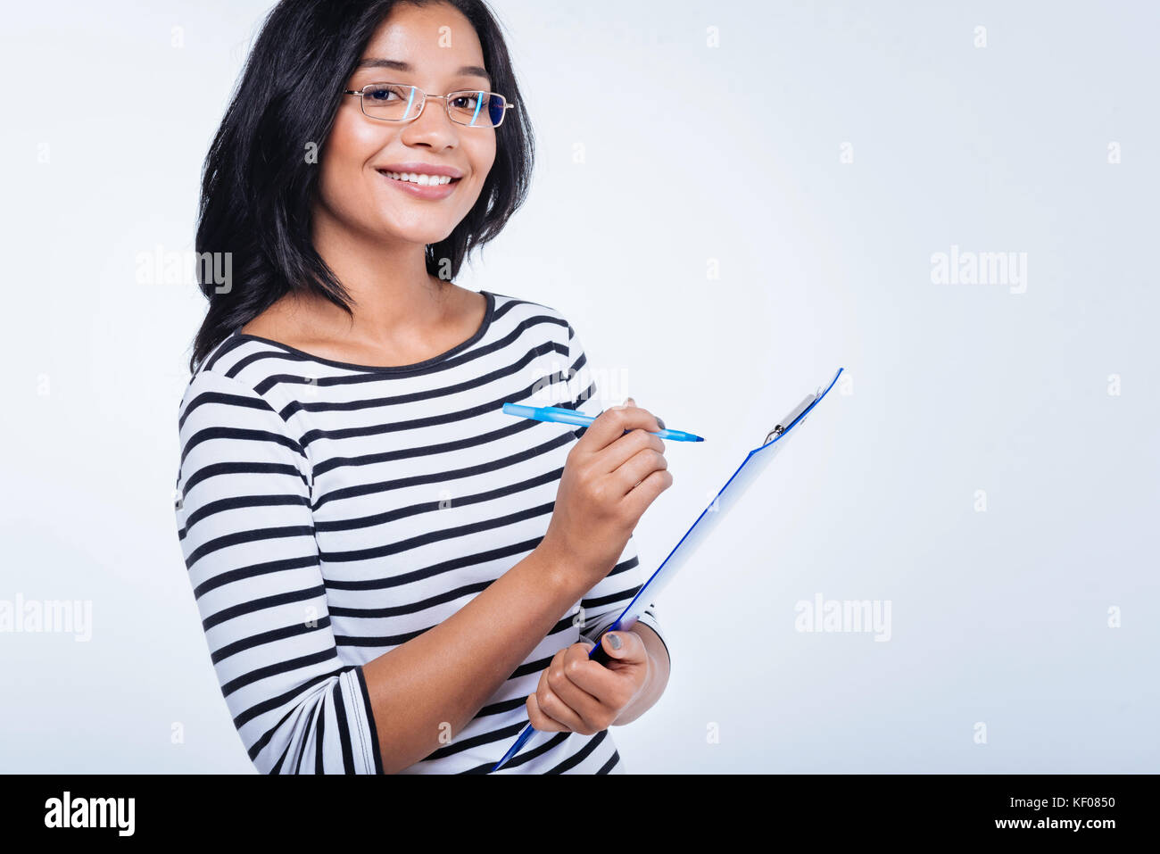 Cheerful woman making notes on sheet pinned to holder - Stock Image