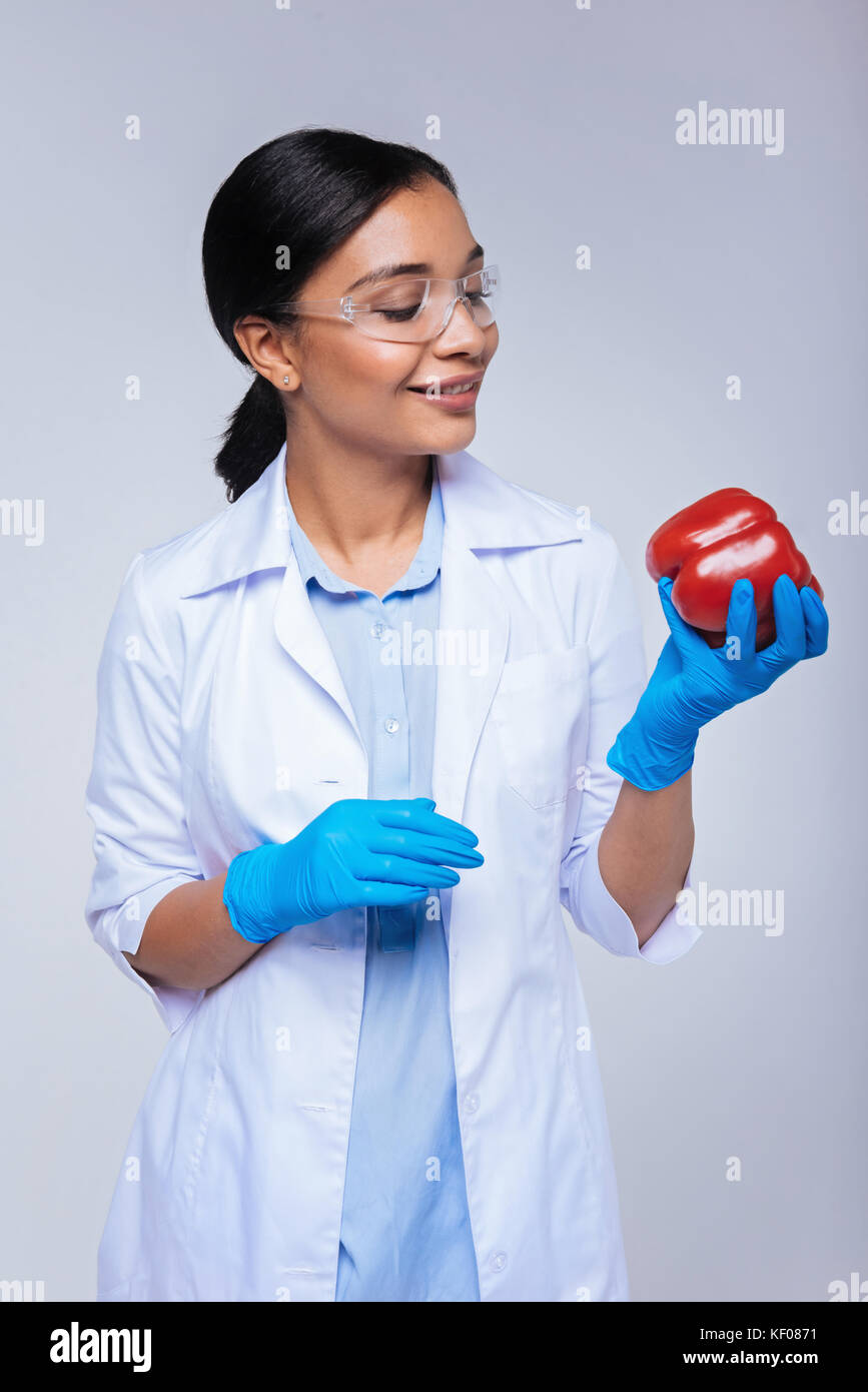 Cheerful lab worker posing with a red bell pepper - Stock Image