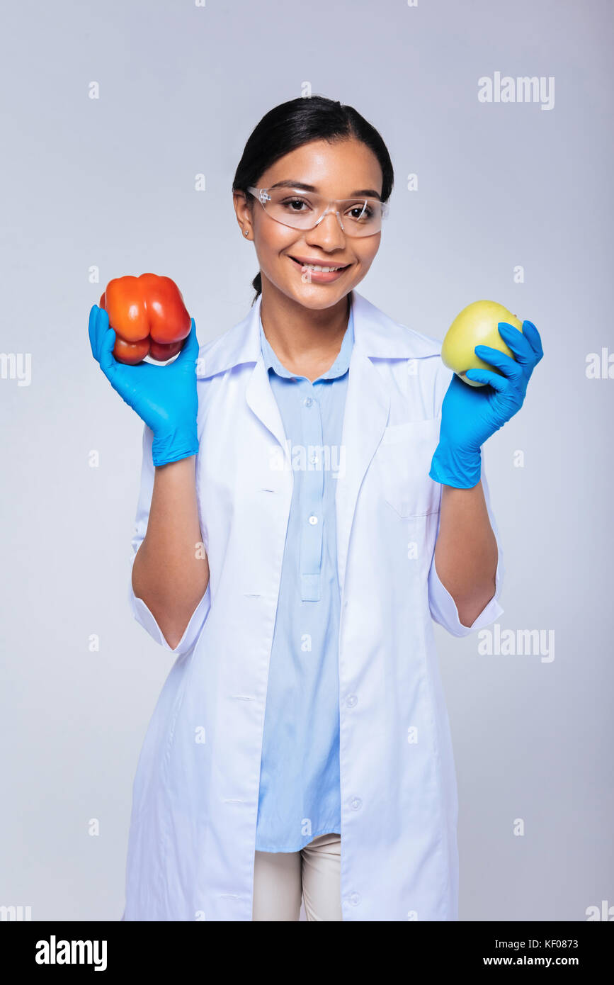 Upbeat lab worker posing with bell pepper and apple - Stock Image