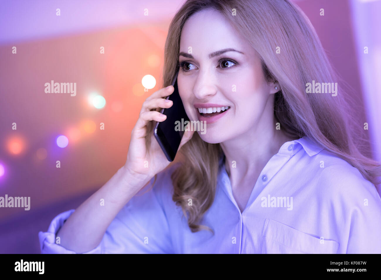 Smiling woman having a conversation on the phone - Stock Image