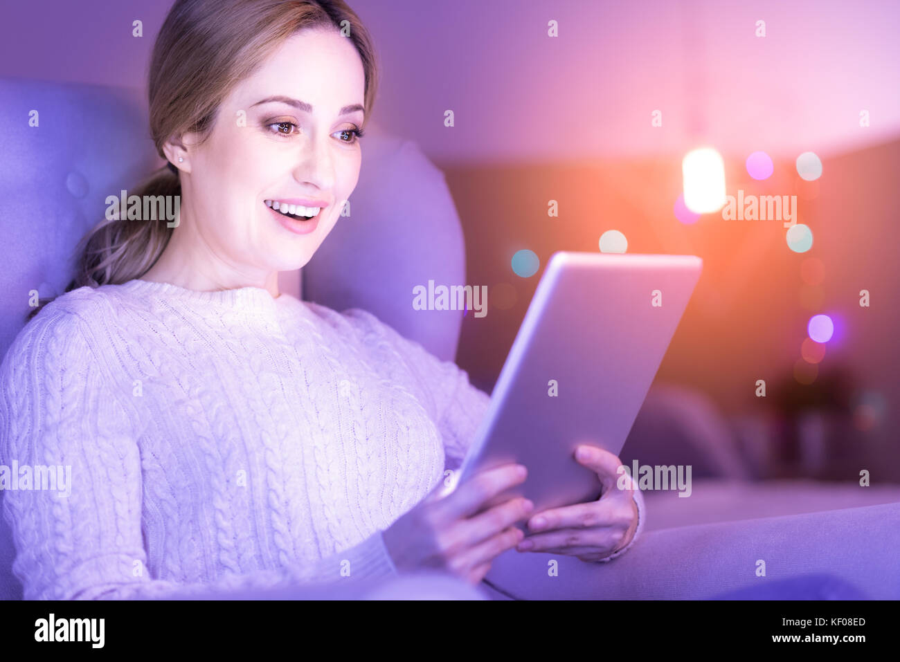 Cheerful woman smiling while looking at her tablet - Stock Image