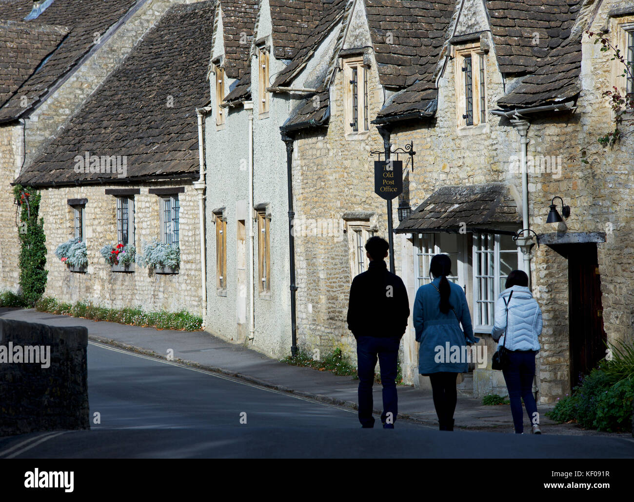 Three Asian tourists exploring the village of Castle Combe, Wiltshire, England UK - Stock Image