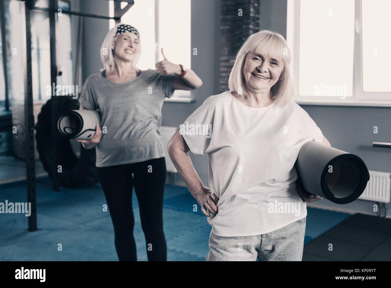 Cheerful elderly women posing with yoga mats - Stock Image