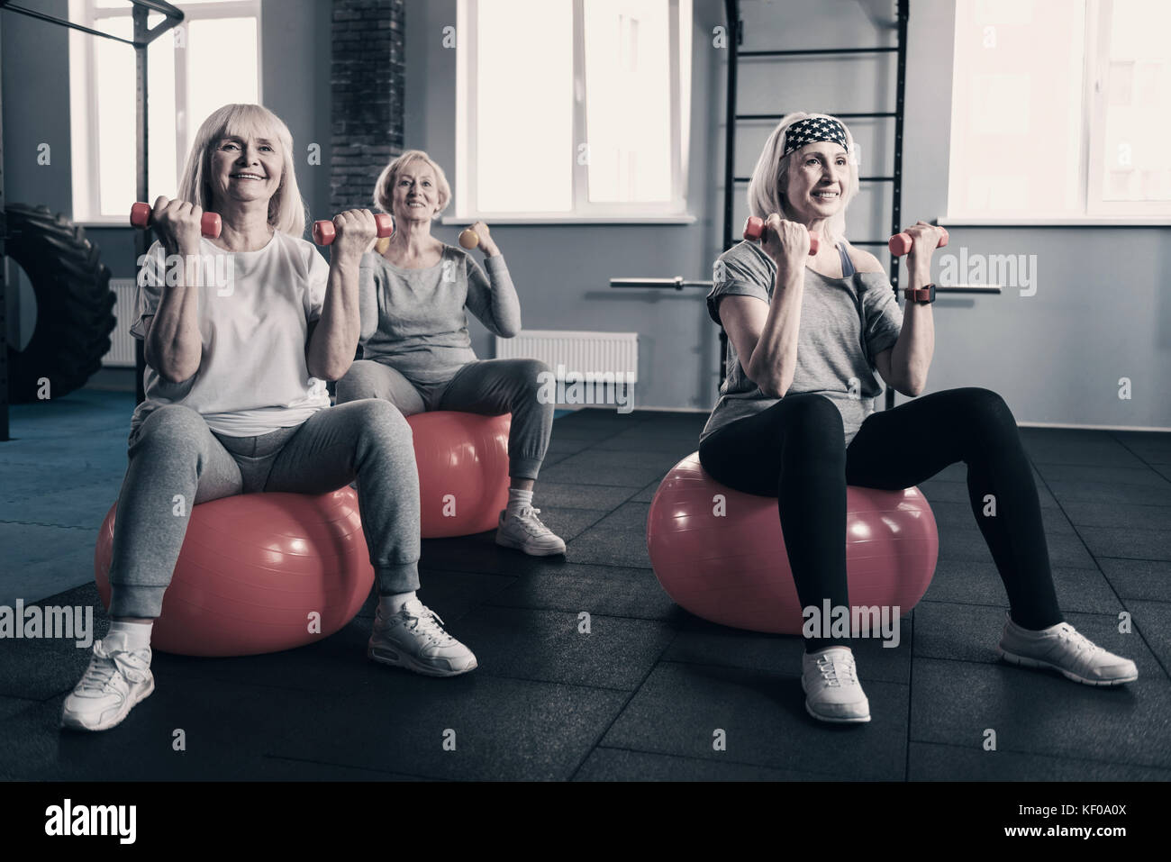 Elderly women working out with dumbbells on exercise balls - Stock Image