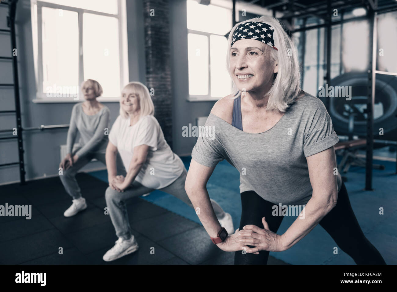 Three senior woman doing stretching together - Stock Image