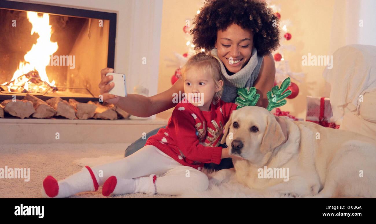Mixed race family taking christmas selfie - Stock Image