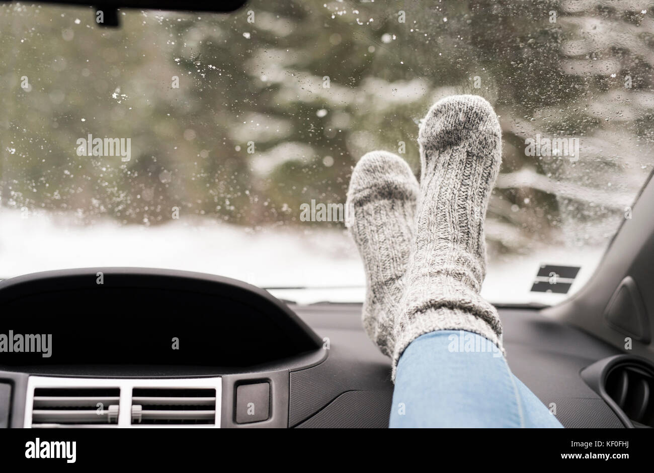 Woman sitting in car with feet up on dashboard - Stock Image