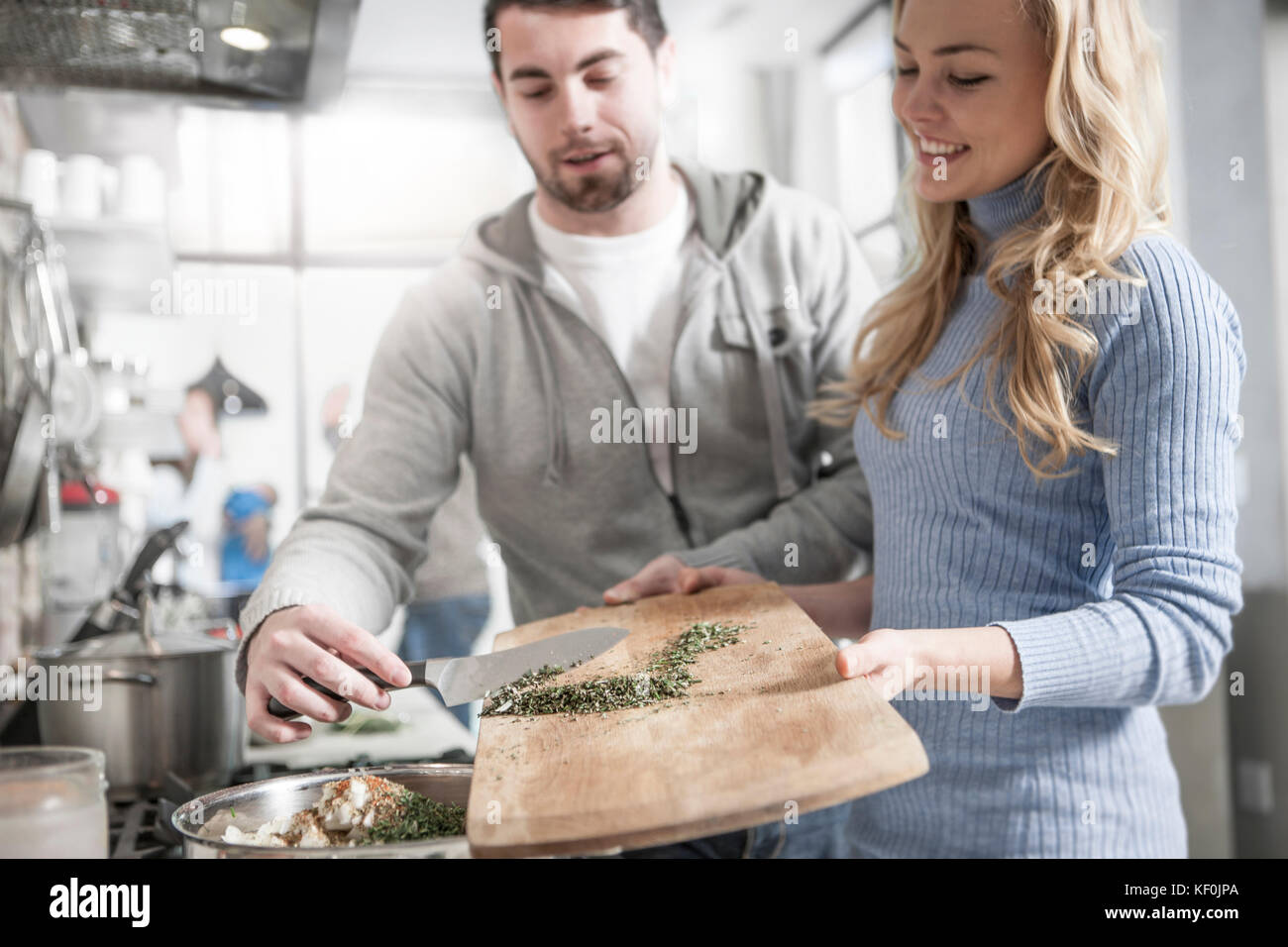 Couple helping one another moving spices in pot - Stock Image
