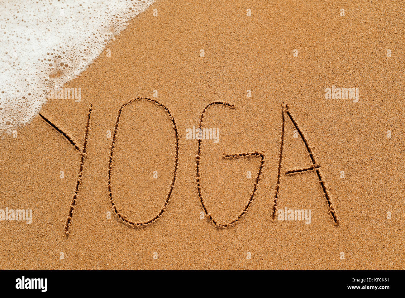 the word yoga written in the sand of a beach, with sea foam in a corner - Stock Image