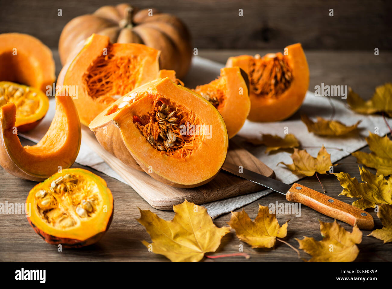 Sliced pumpkin with seeds on a wooden background. Close-up - Stock Image