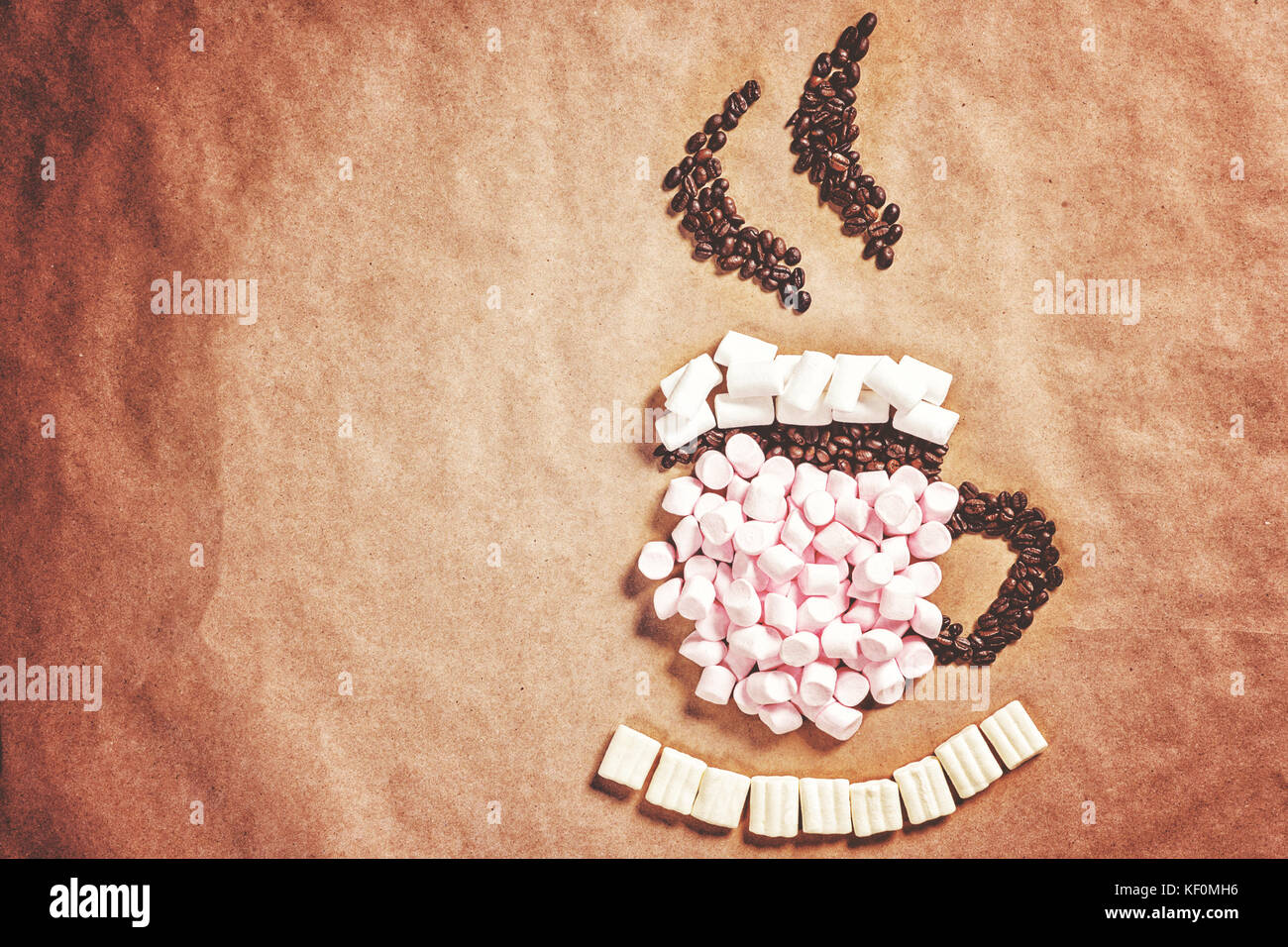 Mug cup of hot coffee cocoa from pink marshmallows and grain coffee on old paper background. Christmas New Year Stock Photo