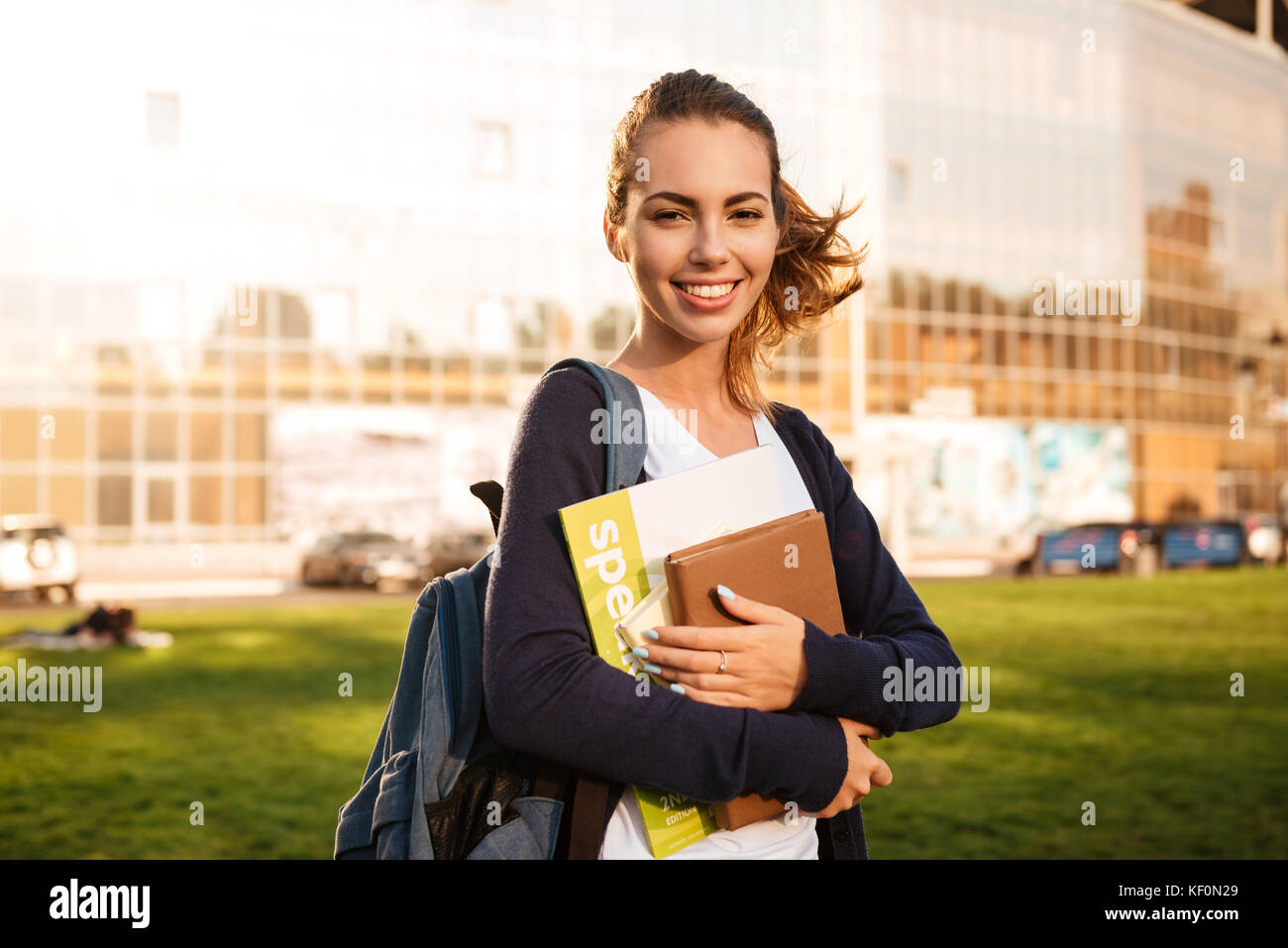 2a4e7d7bab9 Portrait of a joyful brown-haired student girl standing with backpack and  books and looking at camera outdoors