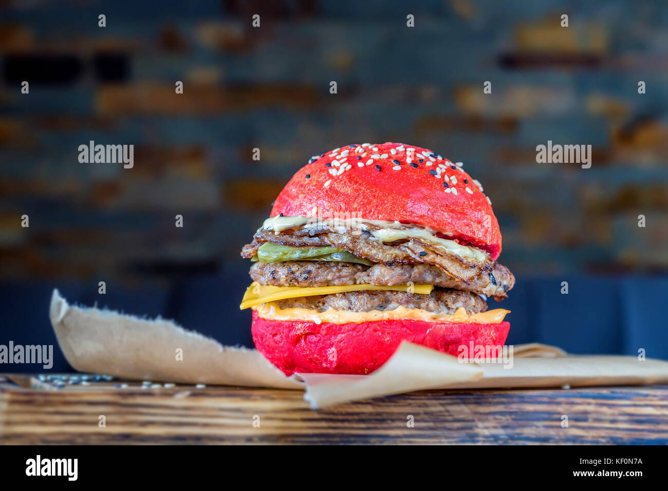 Restaurant burger with red bun on wooden board - Stock Image