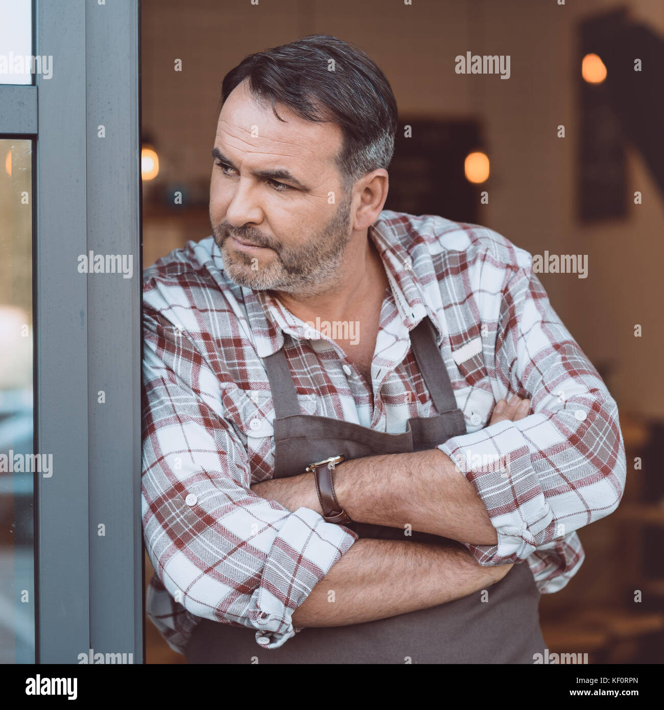 bartender leaning on entrance of cafe - Stock Image