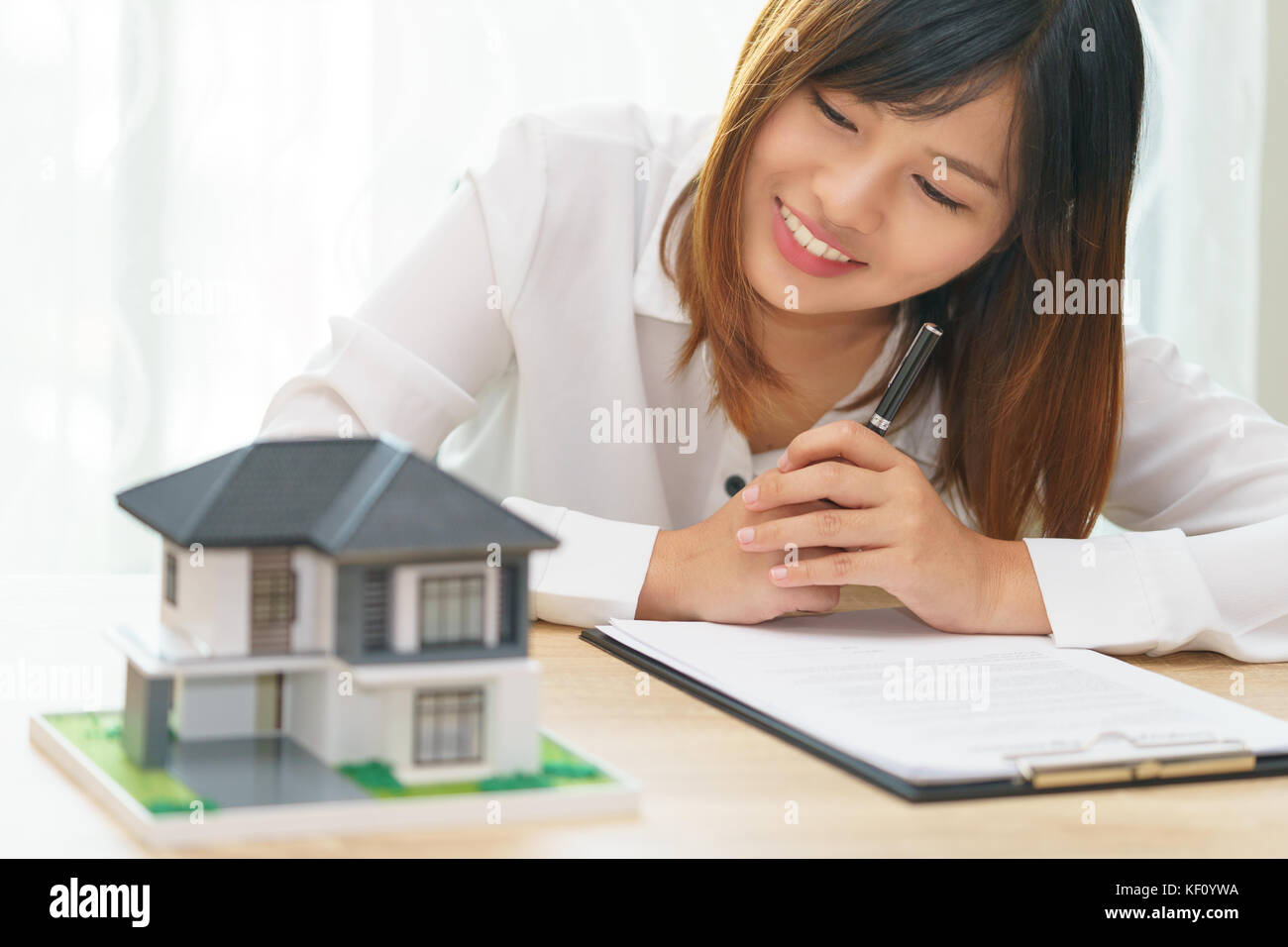 Smile woman looking at home and getting ready to sign contract for investment - satisfy in home - Stock Image