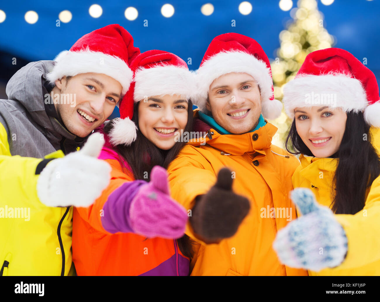 happy friends in santa hats and ski suits outdoors - Stock Image