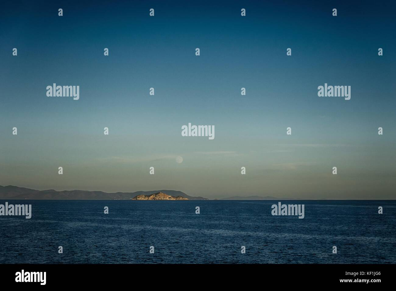Horizontal vintage photo of small rock or island with moon above in Mediterranean Sea with Tuscany coastline in - Stock Image