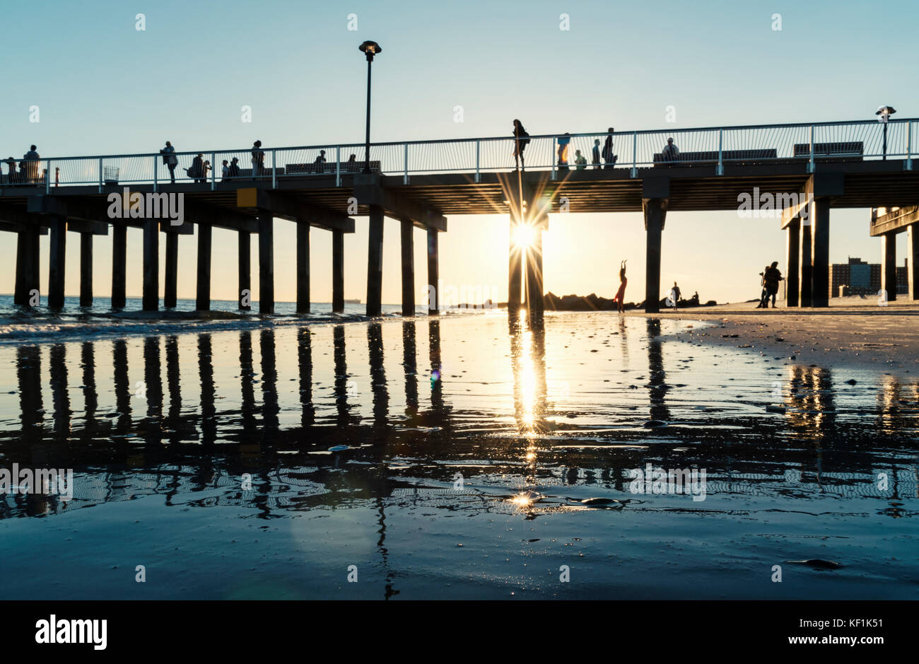 Silhouetted people on and under the Brighton beach pier on Coney island with sunburst - Stock Image