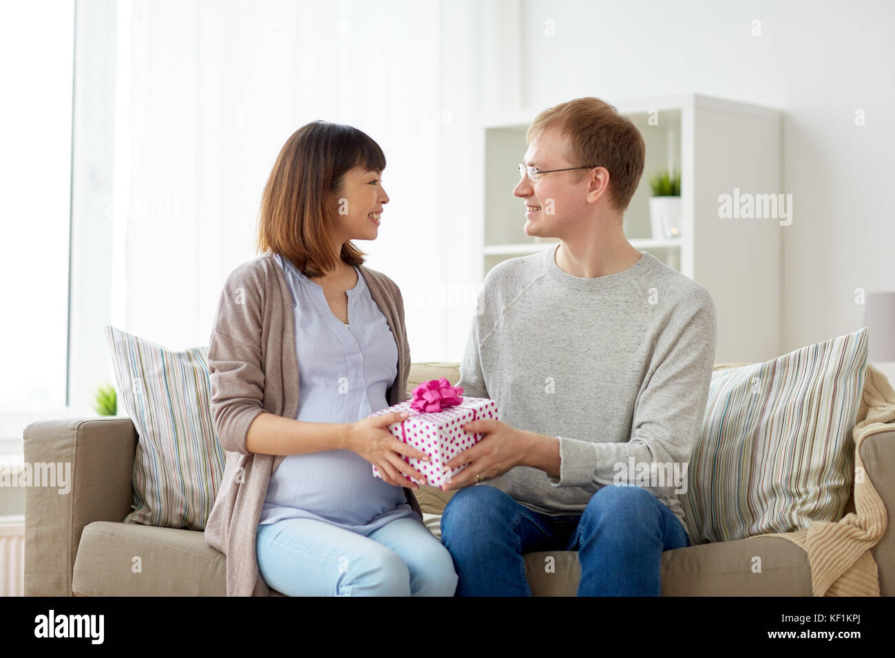 Husband Giving Birthday Present To Pregnant Wife Stock Photo