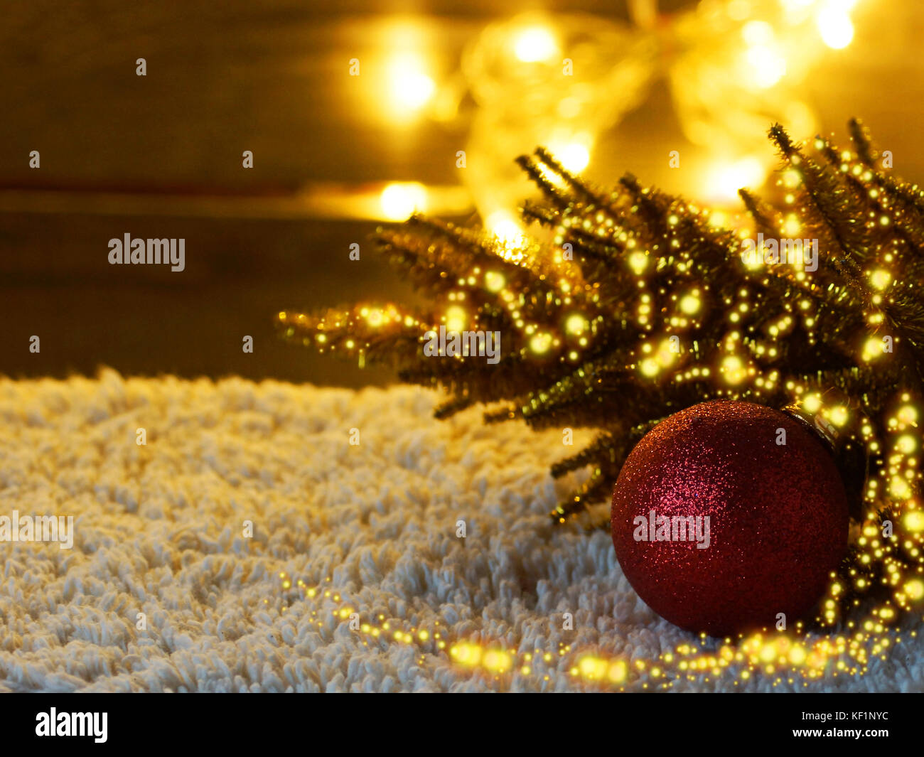 Christmas tree toy red ball against the festive garland. - Stock Image