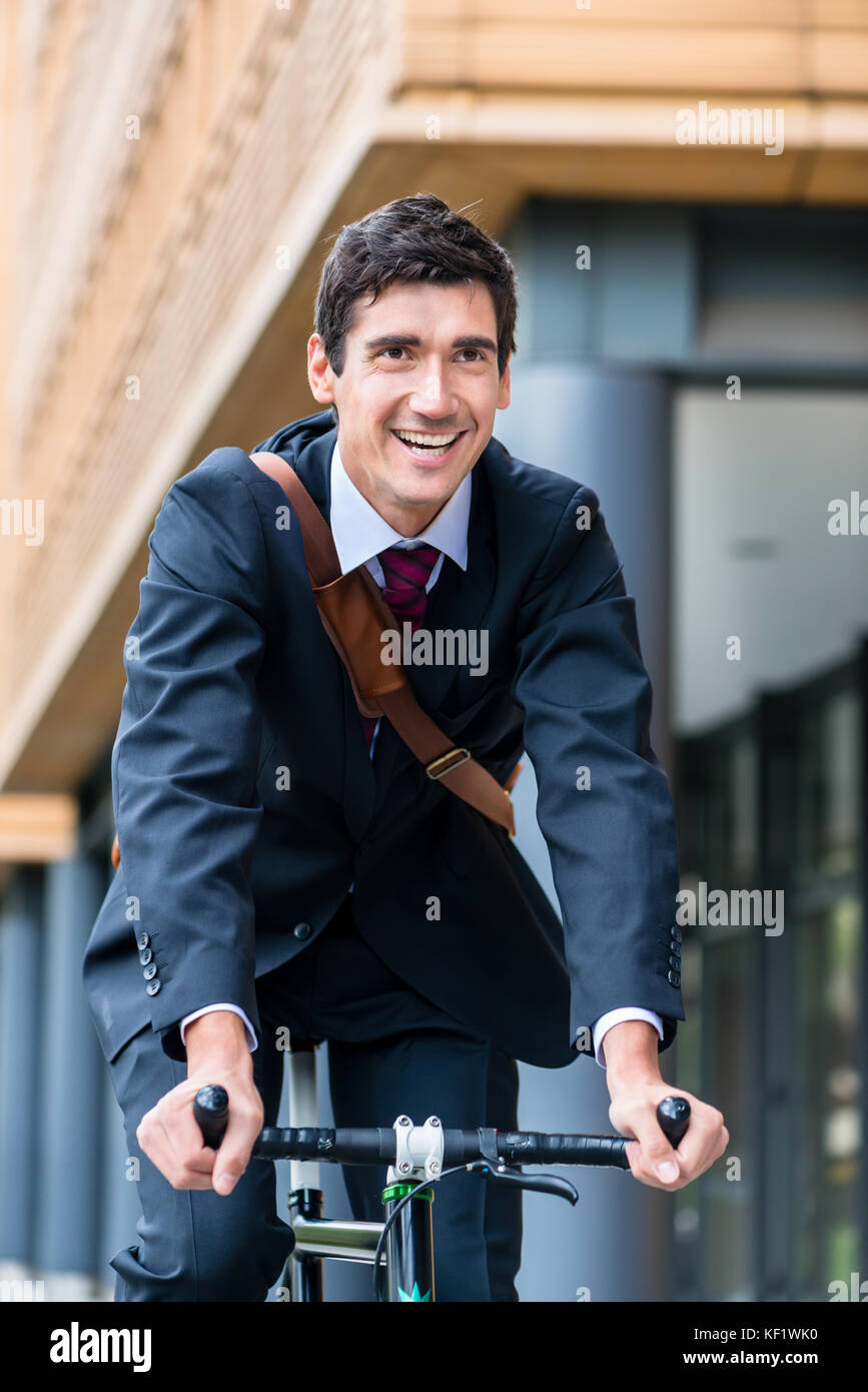 Active young man smiling while riding utility bicycle to his wor - Stock Image