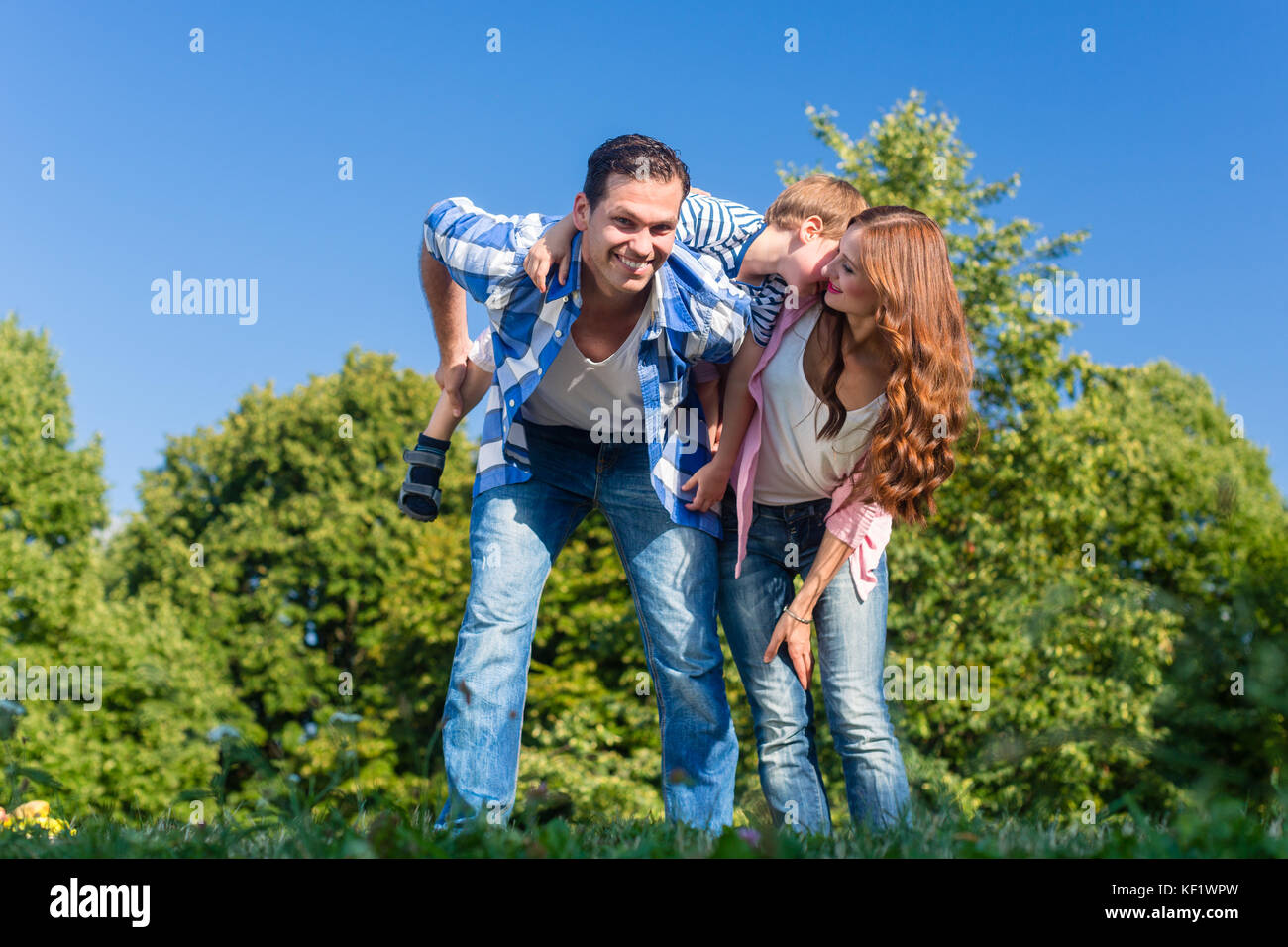Daddy carrying son piggyback on his back  - Stock Image