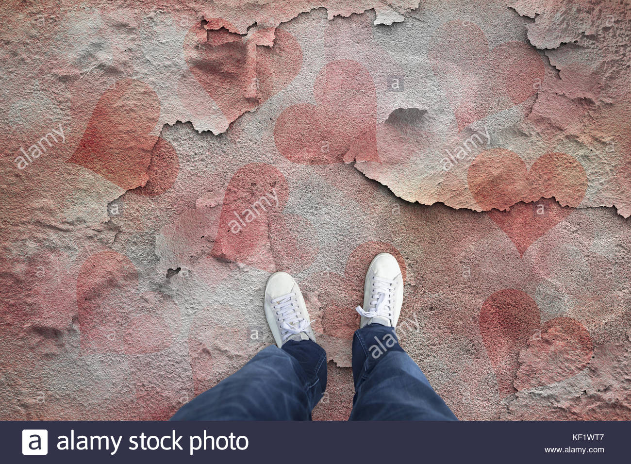 Man standing on the broken and cracked floor with painted purple red colored hearts. Personal perspective used. - Stock Image