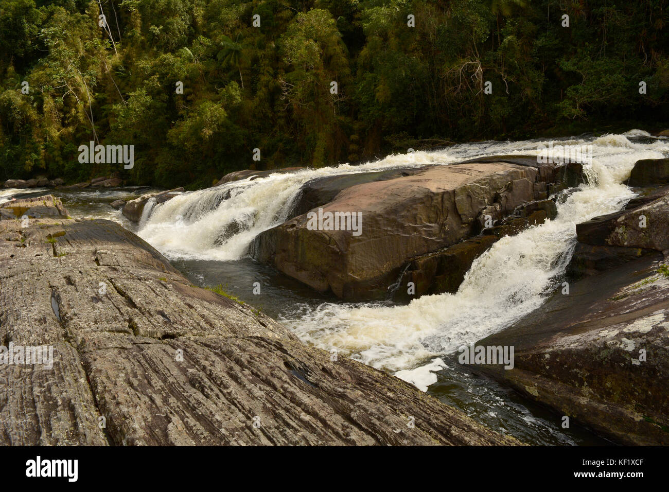 Double waterfall, in the middle of the rocks, with the Atlantic Forest in the background. Stock Photo