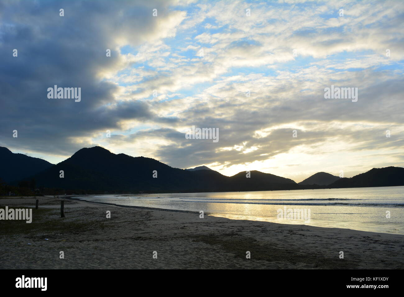 Sunrise behind the mountains, with reflection in the sea, on the beach of Perequê-Açu in Ubatuba, Brazil - Stock Image
