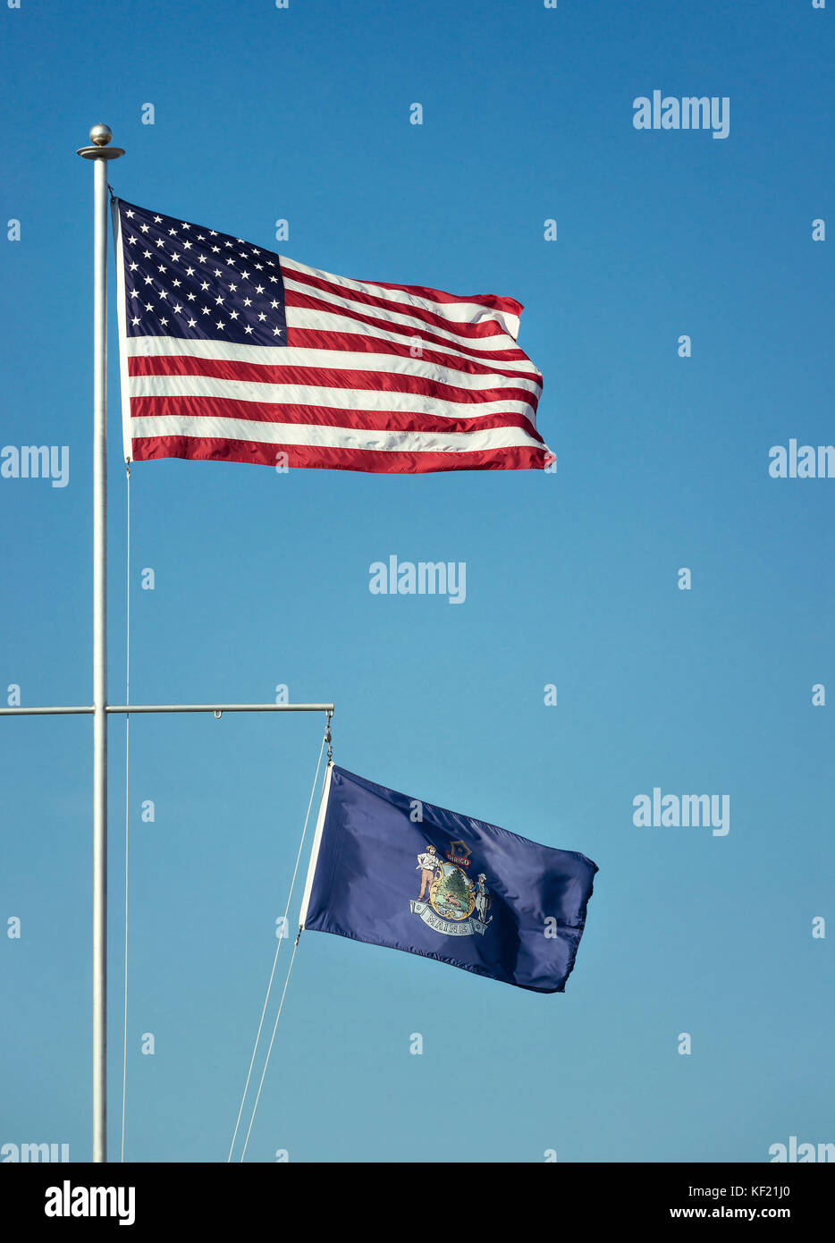 American flag and the State flag of Maine waving in the wind on a flagpole. Blue sky background with copy space. - Stock Image
