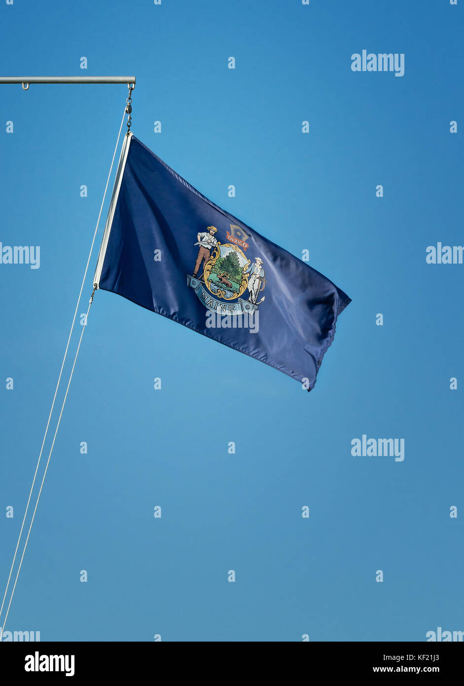 State flag of Maine waving in the wind on a flagpole. Blue sky background with copy space. - Stock Image