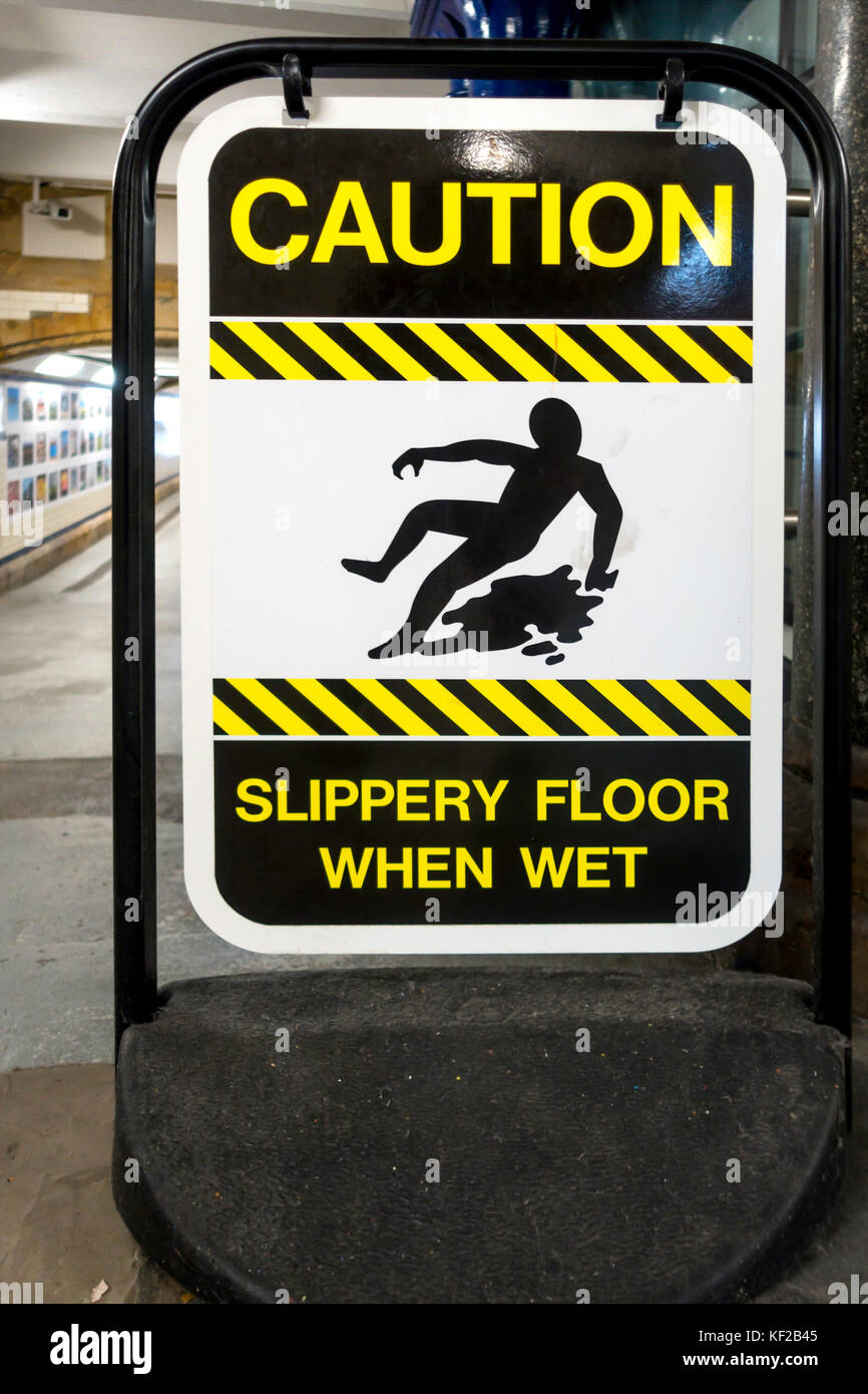 Warning sign Caution  Slippery floor when Wet in a rail train station underpass - Stock Image