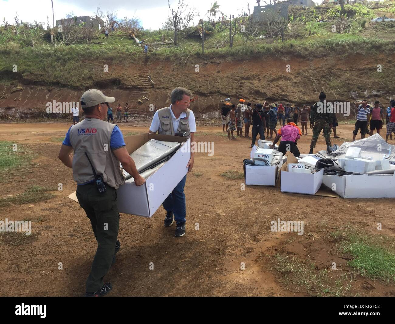 U.S. Agency for International Development (USAID) Development Disaster Assistance Response Team members carry supplies - Stock Image