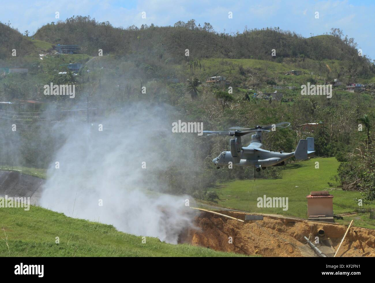 U.S. Marines in a V-22 Osprey aircraft place concrete barriers around the Guajataca Dam as they work to rebuild - Stock Image