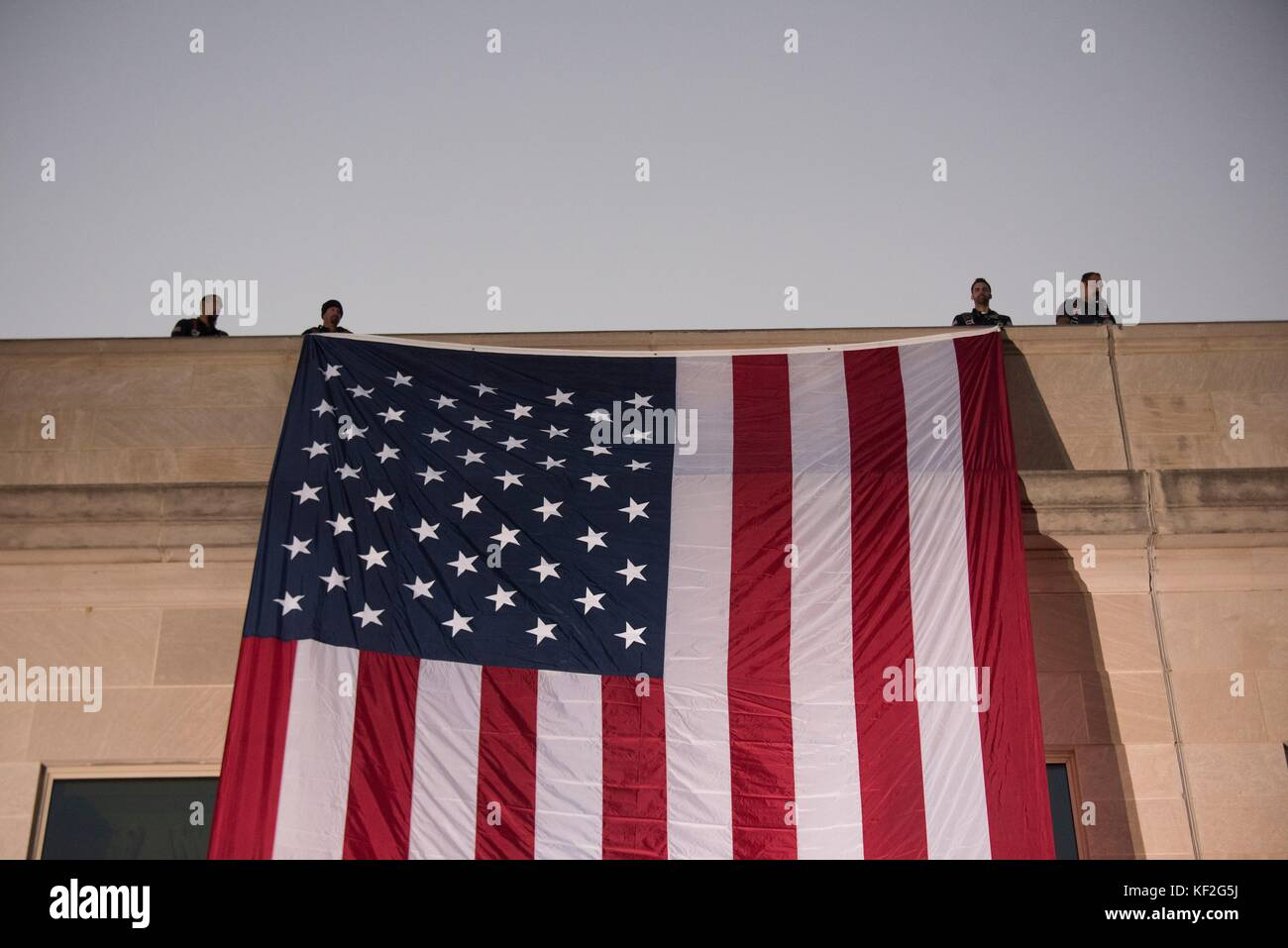 A large American flag is unfurled over the west side of the Pentagon at sunrise to mark the 9/11 attacks during - Stock Image
