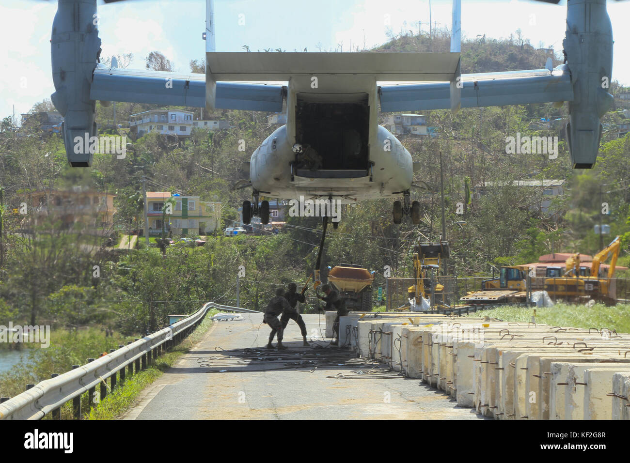 U.S. Marines attach a concrete barrier to a V-22 Osprey aircraft as they work to rebuild the damage to the Guajataca - Stock Image