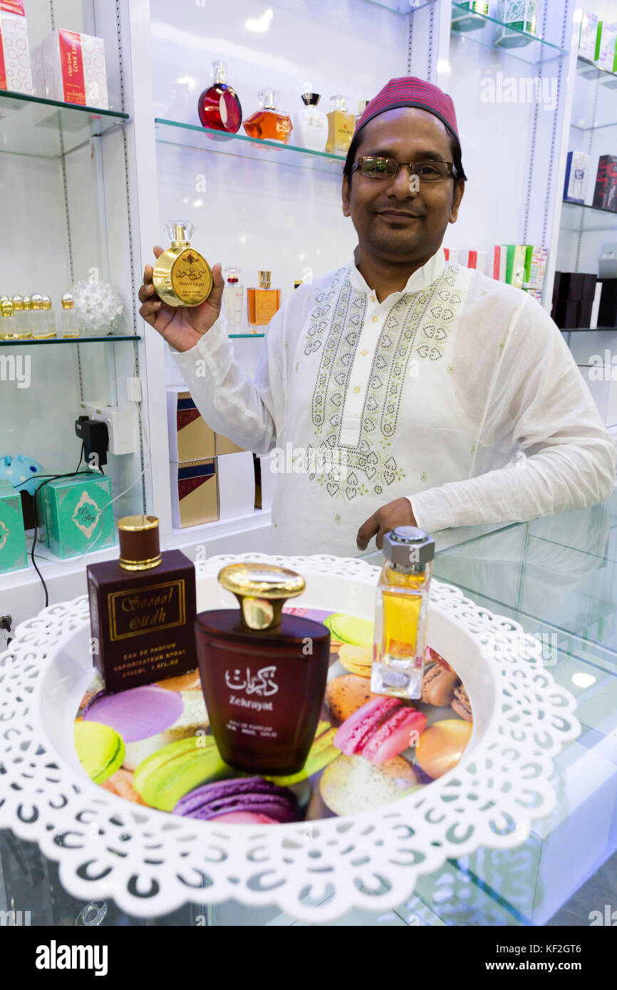 Middle Eastern businessman displaying various bottles of oud perfume in his store located in the Bukit Bintang. - Stock Image