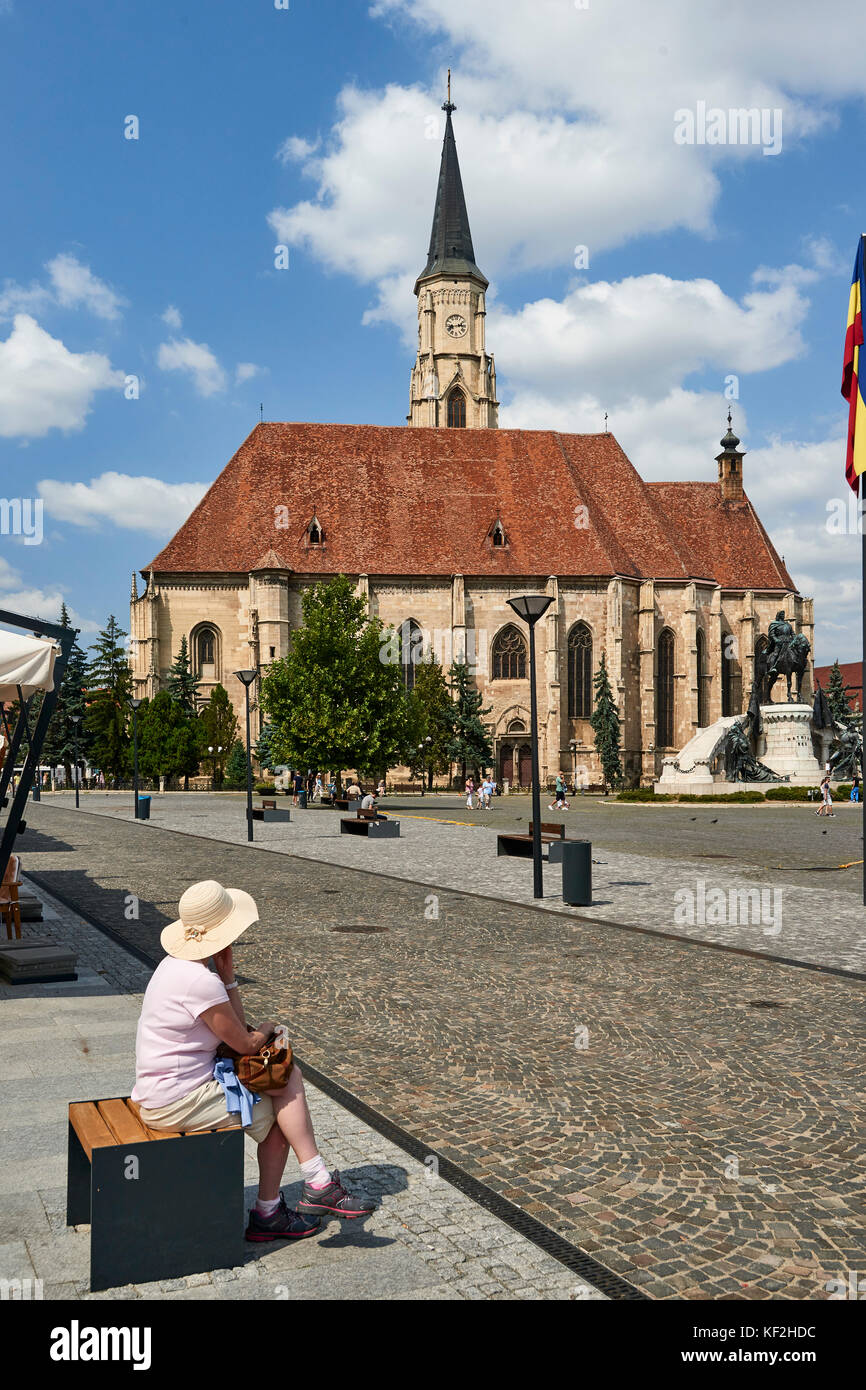St Michael Church and Unirii Square in Cluj - with Linda sitting on public bench and pavement cafe in foreground - Stock Image