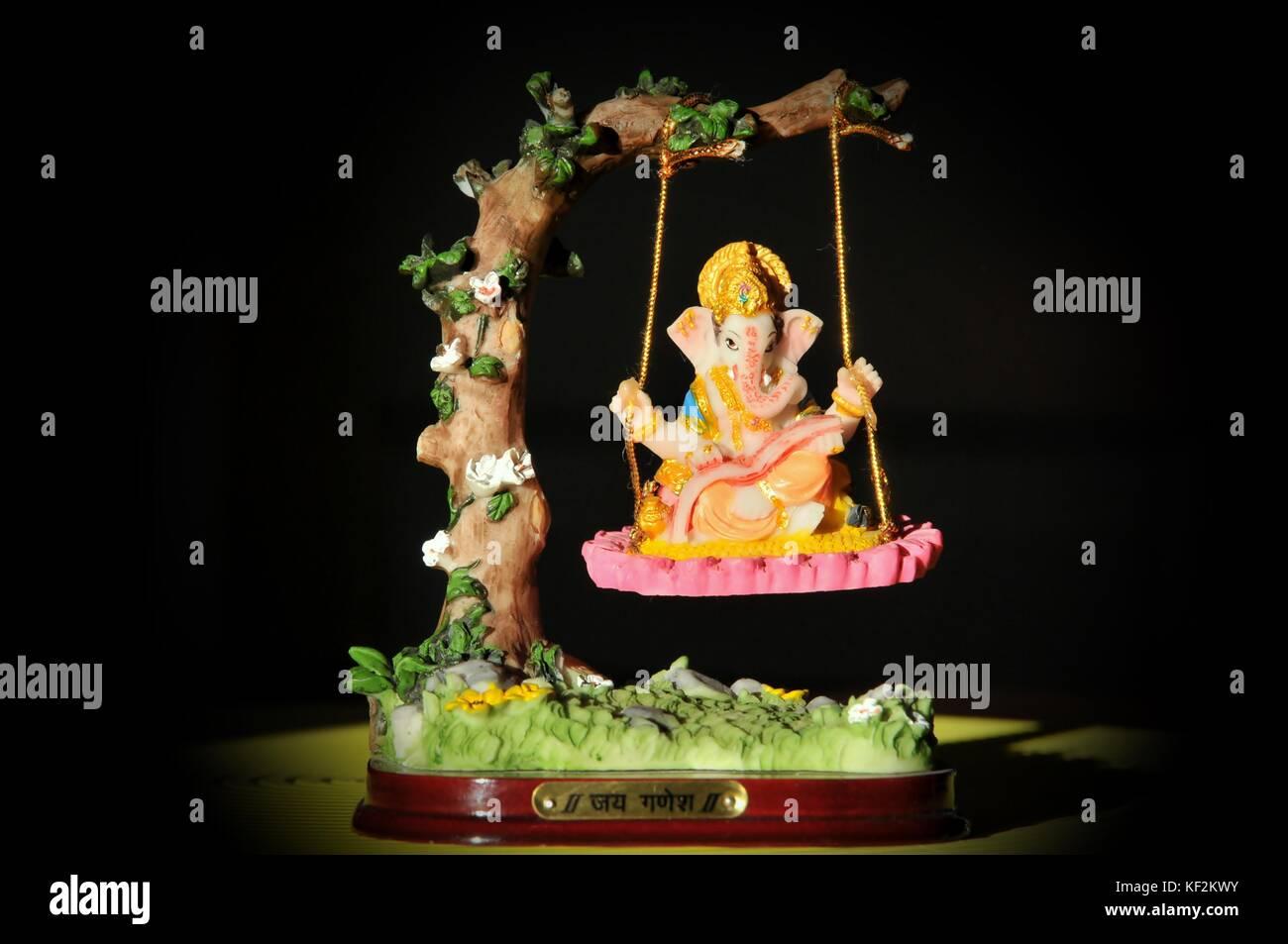 """Lord Ganesha"" Image of  Hindu god on a swing. Stock Photo"