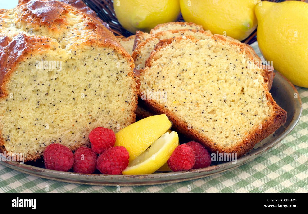 Freshly baked lemon poppyseed poundcake on a plate with ripe raspberries and lemon slices. - Stock Image