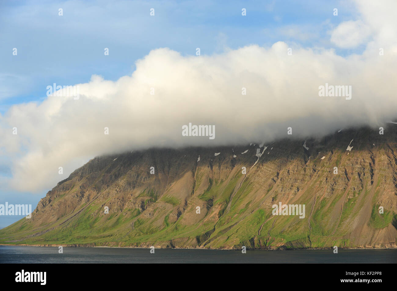 Cloud cover over mountain top and blue skies in Siglufjordur, North Iceland, Scandinavia - Stock Image