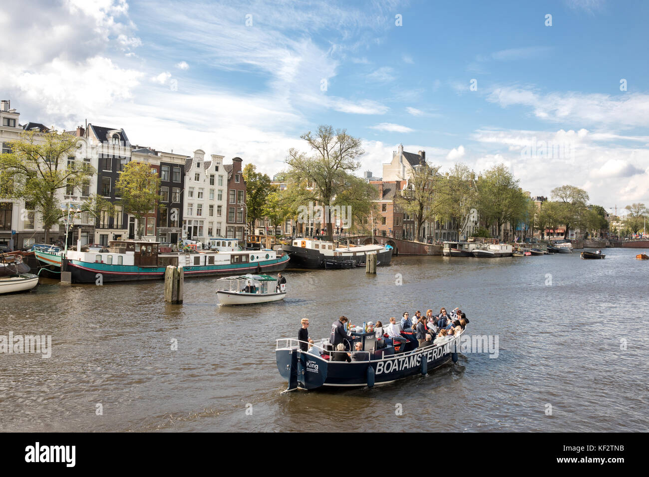 Tourists on a boat trip around Amsterdam's canals, Netherlands - Stock Image